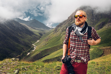 Hiking Adventure Blogger Travel Concept. Handsome Male Traveler With A Beard And Digital Camera Enjoying Summer Mountain View