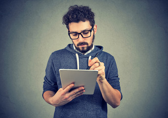 Serious hipster man using tablet computer