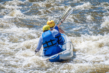Rafting, kayaking. Two sportsmen in sports equipment are sailing on a rubber inflatable boat in a boiling water stream. Teamwork. Water splashes close-up. Extreme sport.