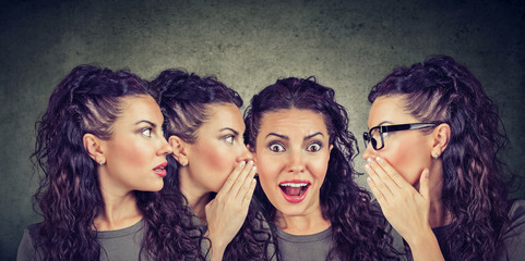 Three young women whispering each other and to a shocked astonished girl
