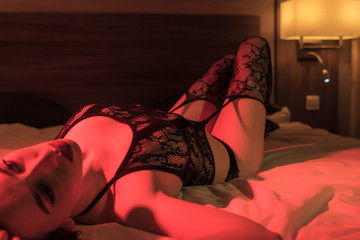 Sexy girl in lacy black underwear and stockings is lying on a bed in red light