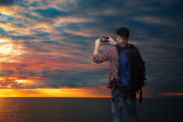 man is taking pictures of the sun setting on the sea