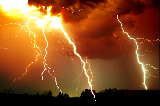 Lightning strike on the dark cloudy sky. Orange, yellow and red toned image