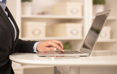 Business woman below chest working on her laptop in a cozy environment