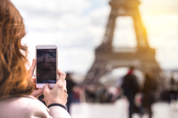 Girl takes pictures of a Eiffel Tower on a smartphone
