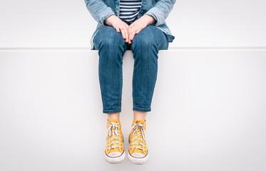 Frau mit gelben Sneaker auf weißer Wand