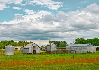 A landscape of a modern farm with a barn, silo , and metal storage buildings under a beautiful dramatic sky.