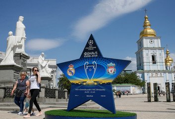 Women walk pass an installation with the logo of the UEFA Champions League final in central Kiev