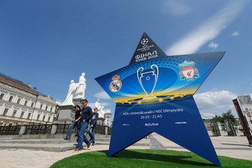 People walk pass an installation with the logo of the UEFA Champions League final in central Kiev