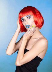 Female in red wig and in comic pop art make-up style on blue background
