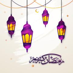 Illuminated hanging lanterns and arabic calligraphic text Ramadan Kareem.