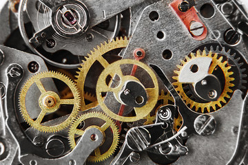 clock mechanism with gears and parts. Macro. Very shallow depth of field. Focus on the left gears
