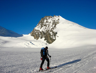 male backcountry skier on his way to the Rimpfischhorn peak in the Alps of Switzerland near Zermatt