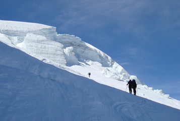 backcountry skiers hiking up a steep glacier and into the sunlight on their way to a high alpine peak near Zermatt