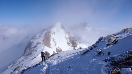 male backcountry skier hiking to a high alpine summit in Switzerland along a rock and snow ridge in light fog