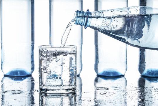 Mineralwasser in ein Glas eingeschenkt, Hintergrund weiß