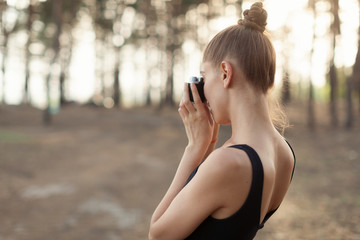 Hipster girl with using vintage photo camera close up, copy space of blank empty mockup, view tourist holding in hands and photograph on device travel on background