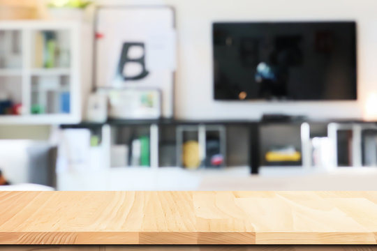 Closeup on wooden table top in the atmosphere of beautiful interior living room blur background.