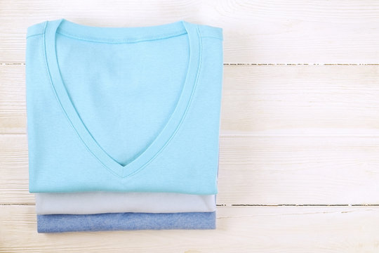 Stack of colorful perfectly folded v neck t-shirts on white wooden texture table background. Pile of different pastel color shirts and sweaters. Background, close up, top view, copy space for text.