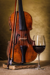 Classical old violin with red wine glass