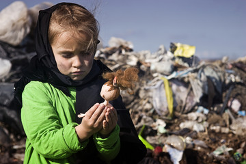 A beggar child in a garbage dump holds a broken doll in his hands