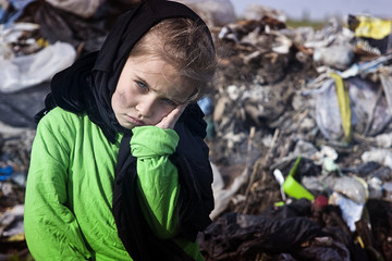 A sad child in a garbage dump looks at passers-by with pain in his eyes