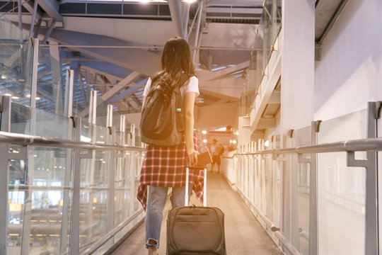 Young woman pulling suitcase in modern airport terminal. Travelling guy with his luggage while waiting for transport. Rear view. holiday vacation concept. Copy space.