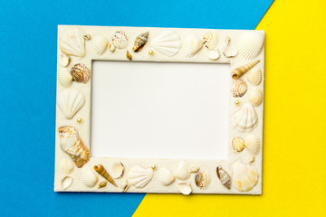 Photo frame with shells on blue and yellow color paper texture background. The concept of a summer vacation.  Summer Flatlay Image
