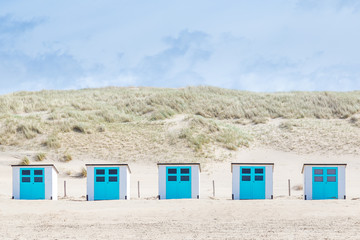 Little white blue  cabins at the beach of Texel. The largest wadden island of the Netherlands.