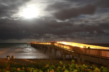 Deerfield Beach Pier Boardwalk Lit Up Illuminated Facing East toward the Atlantic Ocean at Night with a Moonrise Revealing Color in the Cloudy Sky in Late October Near Halloween
