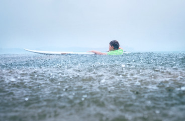 Little boy first step surfer try to stand up on board under tropical rain