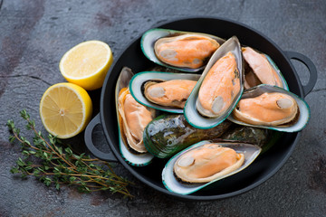 Cast-iron pan with fresh uncooked green mussels, lemon and thyme, studio shot