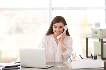 Young woman talking on phone at workplace