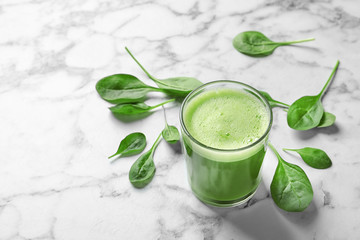 Glass with delicious detox juice and spinach on marble background