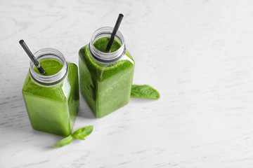 Bottles with delicious detox juice on light background