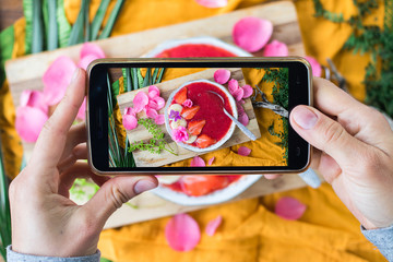 Woman hands take phone photography of food dessert. Smartphone photo of lunch, dinner, food for social media, blogging or instagram. Raw vegan vegetarian healthy food