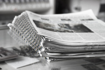 Stack of newspapers on the newspaper stand, close up