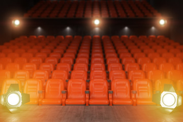 View from the stage of concert hall or theater with red seats and spot light.