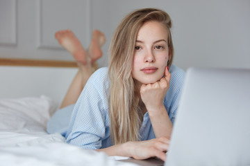 Picture of beautiful young Caucasian female in fashionable pajamas browses internet on laptop computer, connected to wireless internet, makes shopping online, lies on undone bed, feels relaxed