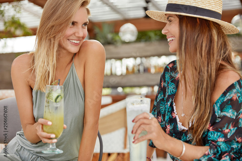 Attractive two females best friends, gossip together, hold