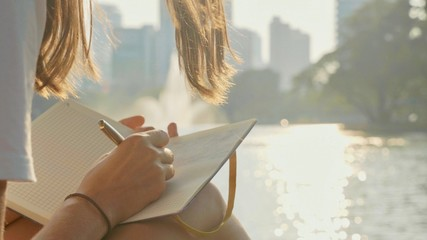 Young woman sitting on the bench in park and writing in diary, close-up