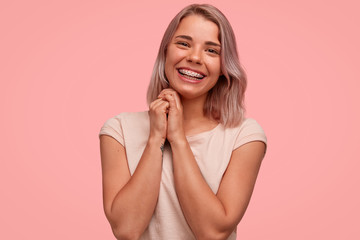 Horizontal shot of good looking female with positive smile, keeps hands together, being in good mood, rejoices winning contest, wears teeth braces, isolated over pink background. Happiness concept
