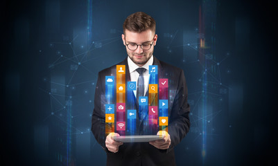Elegant businessman holding tablet with hologram application icons and symbols above