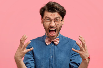 Crazy annoyed male has annoyed expression, argues with strict boss, being irritated with unfair attitude, gestures angrily and screams loudly, isolated on pink background. Negative human emotions.