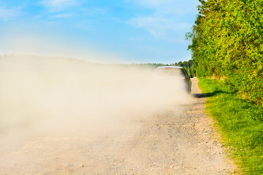 Car ride on a dusty road in a dusty cloud. A car on a gravel road. Comfortable traveling in a passenger car.