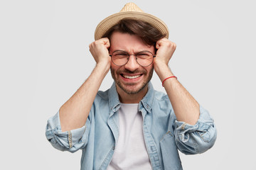 Frustrated desperate bearded young male in casual shirt and hat, has headache and going to cry, has big financial debt, keeps hands on temples and clenches teeth, isolated on white background