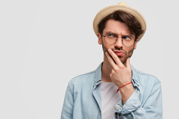 Pensive bearded handsome guy looks thoughtfully aside, holds chin and has serious expression, tries to understand something, isolated over white background with blank space for advertisement