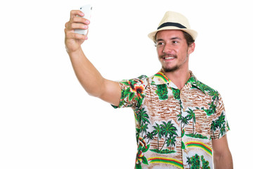 Studio shot of young happy tourist man smiling while taking self