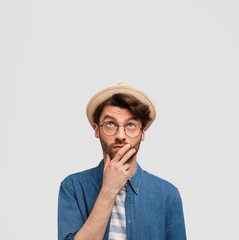 Photo of thoughtful male agricultural worker looks thoughtfully upwards, has stubble, wears straw hat, denim shirt, notices leaking ceiling, isolated on white background, copy space for advertisement