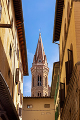 Bell tower of church Badia Fiorentina in Fraternity of Jerusalem abbey. View from old street in Florence city, Italy